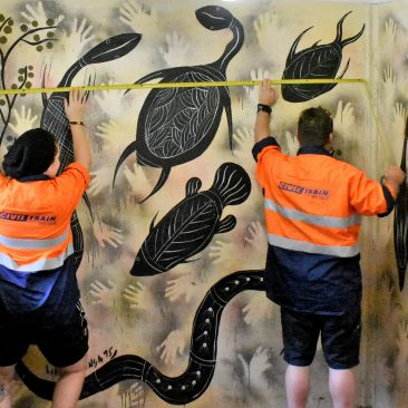 Workers discover an Indigenous artwork and measure it to see if it can be safely removed for transportation